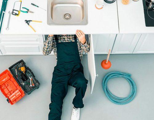 Reformas integrales en Alcala de Henares fontaneros trabajador debajo del lavabo